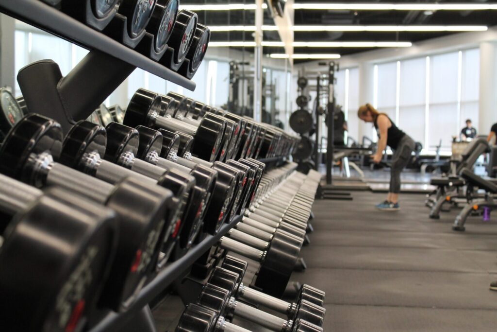 A woman working out in a clean, sanitized gym